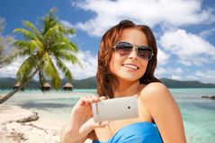 Woman taking selfie by smartphone on beach Royalty Free Stock Image