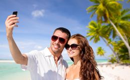 Couple making selfie by smartphone over beach Stock Photos