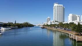 Tropical landscape of Miami tourist coast in a sunny day. Travel and tourism in United States, nature and ocean, blue water and waves, blue sky, buildings in a royalty free stock photography
