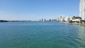 Tropical landscape of Miami coast in a sunny day. Travel and tourism in United States, nature and ocean, blue water and waves, blue sky, buildings in a shoreline royalty free stock photography