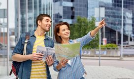 Happy couple of tourists with city guide and map stock photography