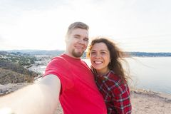 Travel, tourism and vacation concept - Happy married couple taking selfie near a sea royalty free stock photos