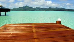 Pier in sea at tropical beach in french polynesia. Travel, tourism, vacation and summer holidays concept - wooden pier with stair and bungalow in sea water at stock video