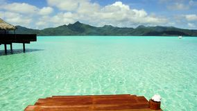 Pier in sea at tropical beach in french polynesia. Travel, tourism, vacation and summer holidays concept - wooden pier with stair and bungalow in sea water at stock footage