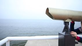Woman looking through the binoculars. Full HD with motorized slider. 1080p. Travel and tourism. Woman looking through the tourist binoculars at the sea or ocean stock video footage