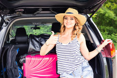 Travel, tourism - woman sitting in the trunk of a car with suitcases, showing thumb up sign, ready to leave for Stock Photos