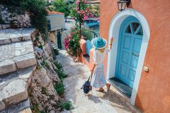 Travel tourist blonde woman with sun hat walking through narrow streets of an old greek town to the beach. Vacation stock photography