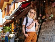Travel tourist girl exploring old streets of Europe city. With backpack royalty free stock image