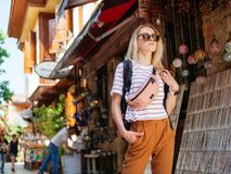 Travel tourist girl exploring old streets of Europe city. With backpack stock photography