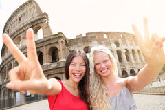 Travel tourist girl friends by Colosseum, Rome. Happy girlfriends tourists showing victory hand sign gesture in front of Coliseum. Beautiful young happy blonde royalty free stock photography