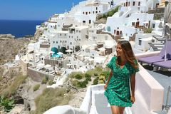 Travel tourist happy woman climbs the stairs in Santorini, Cyclades Islands, Greece, Europe. Girl on summer vacation visiting. Famous tourist destination having royalty free stock image