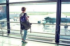 Travel tourist standing with luggage watching at airport window. Unrecognizable woman with short hair looking at lounge looking at airplanes at boarding gate royalty free stock photography