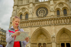 Travel tourist woman. Travel France tourist woman in Paris looking at subway map outdoors. Happy caucasian woman holding travel map in front of Notre Dame royalty free stock photo