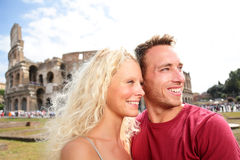 Travel tourists couple in love by Colosseum, Rome. Traveling romantic tourist couple on holidays vacation in Europe. Beautiful blonde women and men in their royalty free stock image