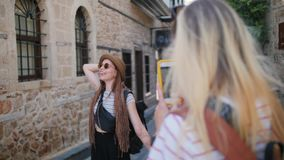 Travel tourist girlfriends laughing taking photo with smartphone in old city of Europe. Travel tourists friends laughing taking photo with smartphone. Women stock footage