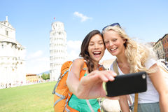 Travel tourists friends taking photo in Pisa. Travel tourists friends laughing taking photo with smartphone. Women girlfriends traveling in Europe smiling joyful Royalty Free Stock Images