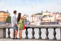 Travel tourists people taking photos in Stockholm. Europe travel tourist people taking pictures. Tourists couple in Stockholm taking smartphone photos having fun Stock Image