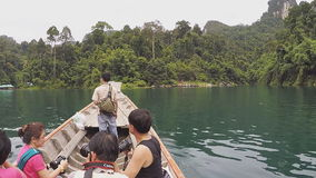 Travel on traditional Thai longtail boat. SURAT THANI, THAILAND - 12 SEPTEMBER 2015 - Unidentified tourists travel on traditional Thai longtail boat in Cheow Lan stock footage