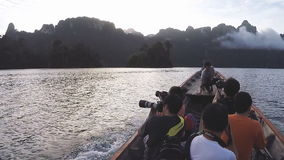 Travel on traditional Thai longtail boat. SURAT THANI, THAILAND - 13 SEPTEMBER 2015 - Unidentified tourists travel on traditional Thai longtail boat in Cheow Lan stock footage