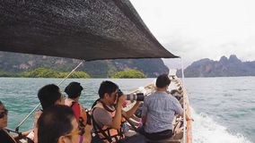 Travel on traditional Thai longtail boat. SURAT THANI, THAILAND - 12 SEPTEMBER 2015 - Unidentified tourists travel on traditional Thai longtail boat for stock video