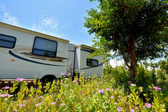 Travel trailer in beautiful camp. With tree and flower, shown as enjoy wonderful trip and holiday, or featured living environment Stock Photo