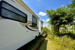 Travel trailer in camp. Travel trailer in beautiful camp with tree and flower, shown as enjoy wonderful trip and holiday, or featured living environment Royalty Free Stock Images