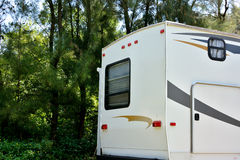 Travel trailer in forest camp. Shown as enjoy wonderful trip and holiday, or featured living environment Stock Photography