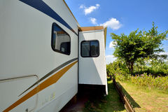 Travel trailer in sunshine day. Travel trailer under blue sky, in camp with tree and flower, shown as enjoy wonderful trip and holiday, or featured living Stock Photos