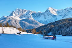 Red train in snow-covered Alpine landscape Stock Photos
