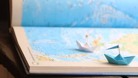 Travel, travelling or tourism concept, paper boats on the sea atlas. Travel and tourism concept, paper boats on the map stock footage