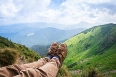 Travel, trekking. Foot traveler in shoes, against the backdrop of mountains. Horizontal frame. Travel, trekking. Foot traveler in shoes, against the backdrop of royalty free stock image