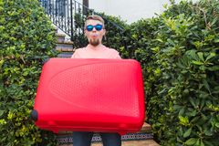 Travel, trip and holidays concept - young man with red suitcase in sunny glasses surprised.  royalty free stock photos