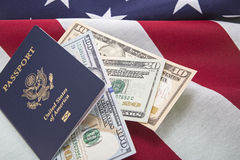 Travel USA currency bills passport US flag success. The United States of America passport book and USA paper money rests on the American flag. The concept is Stock Photos