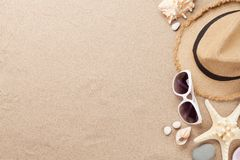 Travel vacation background concept with sunglasses and beach hat on sand backdrop. Top view with copy space. Flat lay royalty free stock photo