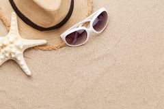 Travel vacation background concept with sunglasses, hat and starfish on sand backdrop. Top view with copy space. Flat lay royalty free stock photography