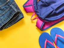 Travel vacation background. Flip flops, backpack, jeans on a yellow background. Flat lay stock photography