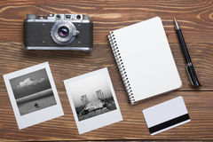 Travel, vacation concept. Camera, notepad, pen, credit card and photography on office wooden desk table. Top view with Stock Image