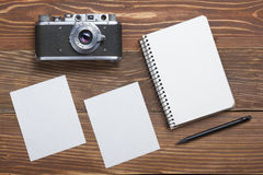Travel, vacation concept. Camera, notepad, pen and photography on office wooden desk table. Top view with copy space for stock images