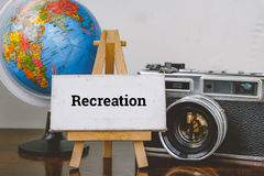 Travel and vacation concept image,word RECREATION and with easel ,globe and vintage camera layout on wooden desk. Selective focus shot and faded effect Royalty Free Stock Image