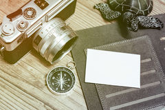 Top view of vintage camera, compass and planner book layout on wooden floor. Royalty Free Stock Images