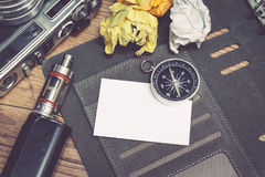 Top view of vintage camera, crumple paper,electronic cigarette and planner book layout on wooden floor. Stock Images
