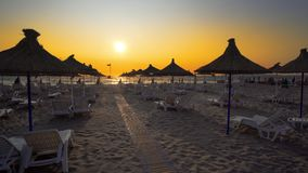 Wonderful sunset at the empty beach with loungers. TRAVEL VACATION CONCEPT. Wonderful sunset at the empty beach with loungers and wooden sheds royalty free stock image