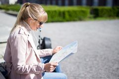 Travel and vacation concept - young woman holding tourist map sitting in park royalty free stock images