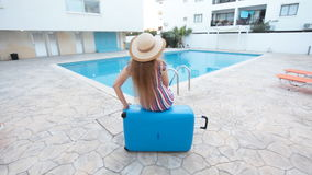 Travel vacation concept. Young woman near swimming pool. With suitcase stock video