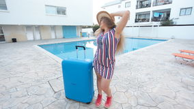 Travel vacation concept. Young woman near swimming pool. With suitcase stock video footage