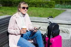 Travel and vacation concept - young woman sitting in park with suitcase royalty free stock images