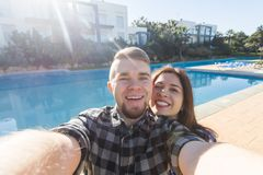 Travel, vacation and holiday concept - Beautiful love couple having fun taking selfie near a swimming pool.  stock photo