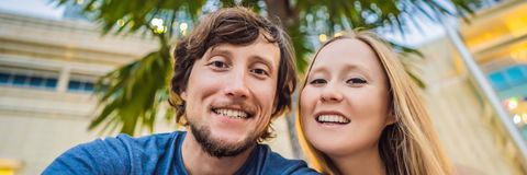 Travel, vacation and holiday concept - Happy couple having fun taking selfie over park with palms background and. Skyscrapers. BANNER, LONG FORMAT royalty free stock images