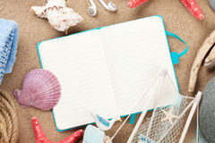 Travel and vacation notepad with items over sand Royalty Free Stock Photos