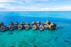 Travel vacation paradise aerial image with overwater bungalows in coral reef sea. Travel vacation paradise aerial drone video with overwater bungalows in coral royalty free stock photo